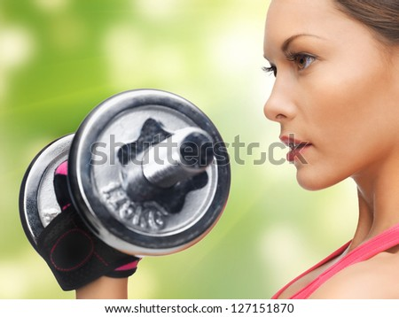 picture of beautiful sporty woman with dumbbell - stock photo