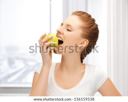picture of beautiful teenage biting a green apple - stock photo