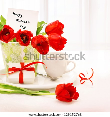 Picture of beautiful tulips pot with gift box and cup of tea on the table at home, breakfast for mommy, happy mothers day, morning drink, romantic still life, indoor decorations, fresh red flowers - stock photo