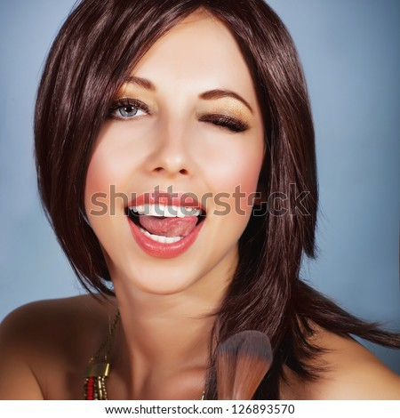 Picture of beautiful woman doing makeup, closeup portrait of glamorous girl applying brush for blush to make perfect complexion, seductive visage, playful expression of face, luxury lifestyle - stock photo