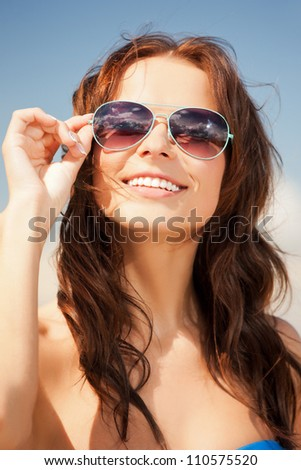 picture of beautiful woman in sunglasses on a beach - stock photo