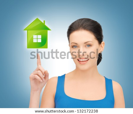 picture of beautiful woman pointing her finger on green house - stock photo
