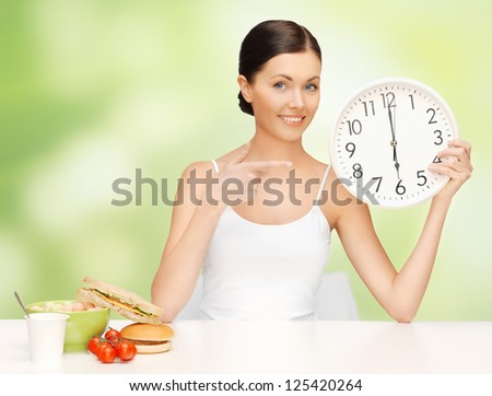 picture of beautiful woman with big clock - stock photo