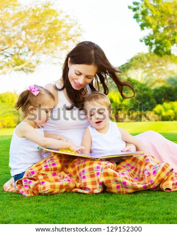 Picture of beautiful woman with daughter and son sitting down on green grass field and read fairytale, cheerful mother and two pretty kids enjoying book on backyard in spring, happy family concept - stock photo