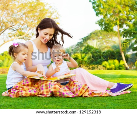 Picture of beautiful woman with daughter and son sitting down on green grass field and read fairytale, cute female with two little children enjoying book outdoors, preschool education, happy family - stock photo