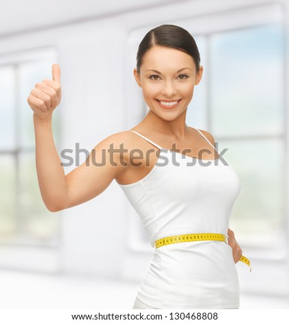 picture of beautiful woman with measuring tape - stock photo