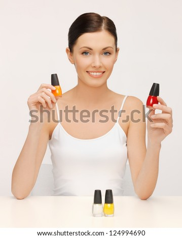 picture of beautiful woman with nail polish bottles - stock photo