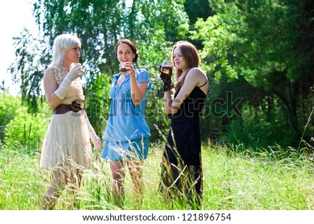 Picture of beautiful women smiling  and drinking in the forest - stock photo