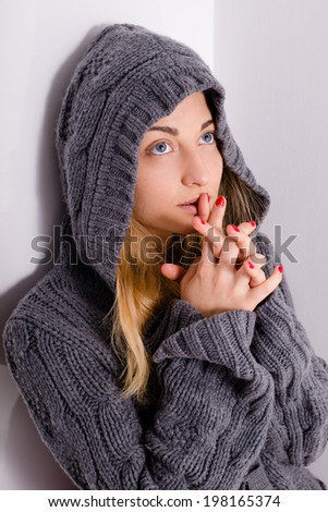 picture of beautiful young blond woman fair hair blue eyes girl in hood holding hands in praying & looking up at copy space on light purple wall background - stock photo