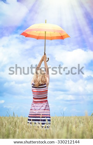 Picture of beautiful young lady rising colorful umbrella on golden wheat field. Backview of pretty girl in striped dress on sunrays countryside background.