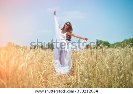 Picture of beautiful young lady standing on golden wheat field. Pretty girl in white dress and sunglasses with raised hands on sunny countryside background. - stock photo