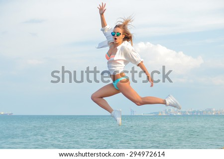 Picture of beautiful young woman having fun in high jump over outdoors copy space background - stock photo