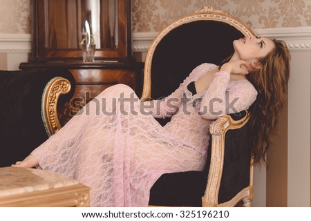 Picture of beautiful young woman sitting in classic armchair. Sexy lady in black lingerie under lace dress on luxury room background. - stock photo