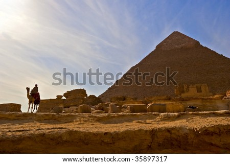 Picture of bedouin on camel near great egyptian pyramid in Giza, Cairo with impressive skies and clouds - stock photo