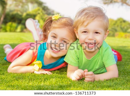Picture of brother and sister having fun in the park, two cheerful children laying down on green grass, little girl and boy playing outdoors, best friends, happy family, love and happiness concept