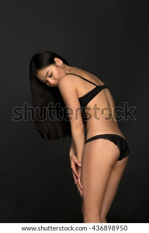 Picture of brunette lady looking down. Attractive fashion asian model in black lingerie demonstrating her gorgeous back in studio. - stock photo