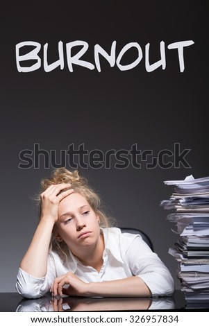 Picture of burnout female office worker and her paperwork - stock photo
