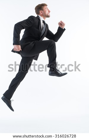 Picture of businessman running up imaginative stairs isolated on white. Serious man in black business suit is in a hurry. - stock photo