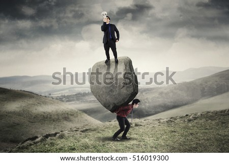 Picture of businessman shouting with megaphone and looking at the camera while standing on a boulder and his partner on the hill