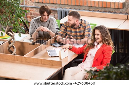 Picture of businesswoman in red jacket sitting at table and listening to her colleagues. Business people working in office. - stock photo