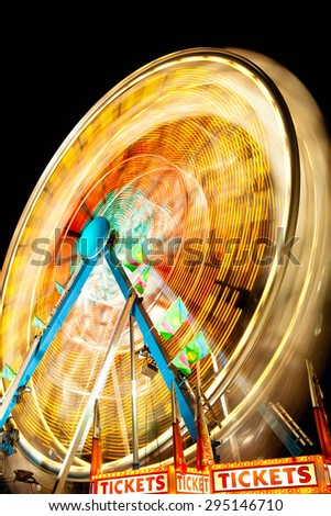 Picture of Carnival Ferris Wheel at night spinning motion blurred. - stock photo