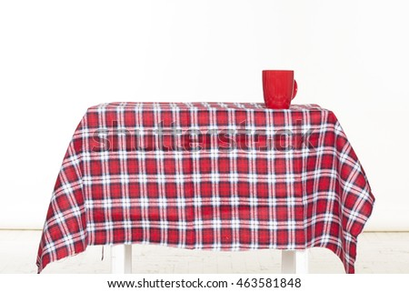 Picture of checkered table with red cup on it