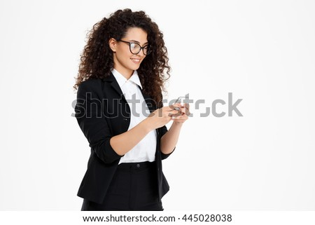 Picture of cheerful curly business girl wearing glasses looking at phone over white background - stock photo