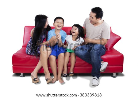 Picture of cheerful family sitting on the sofa while having fun and laughing together, isolated on white background