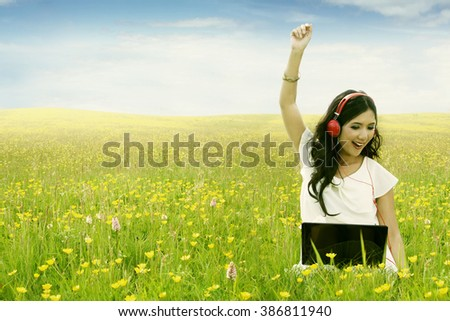 Picture of cheerful young woman enjoy music with laptop and headphone while sitting on the meadow at springtime