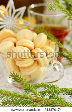 Picture of Christmastime cookies with cup of tea on wooden table, New Year sweets still life on dark glowing brown background, little decorative Christmas tree, candy cane