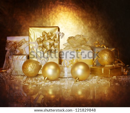 Picture of Christmastime gift boxes isolated on dark golden background, luxury Christmas decorations, seasonal shopping, shiny balls, festive ornament, New Year present, holiday greeting card