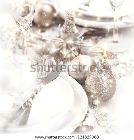 Picture of Christmastime table setting, white festive plate with knife and fork, shiny silver decoration, candle light, home interior, beautiful holiday dinnerware, romantic New Year dinner - stock photo