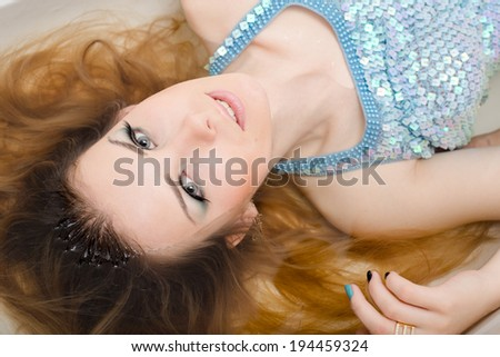 picture of closeup portrait on glamor fashion girl beautiful blond young woman having fun relaxing in clear water of bathtub & looking at camera sensually   - stock photo