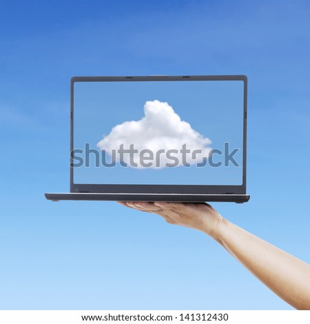 Picture of cloud from laptop screen under blue sky - stock photo