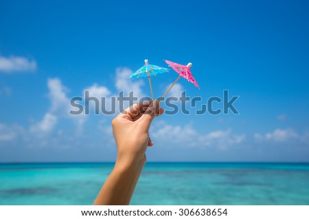 Picture of cocktail umbrella on the tropical beach, vacation. Traveller dreams concept - stock photo