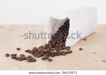 Picture of coffee beans rolling out of a bag - stock photo