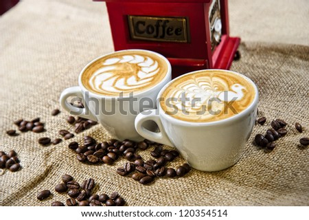 Picture of coffee cups in front of manual coffee grinder. - stock photo