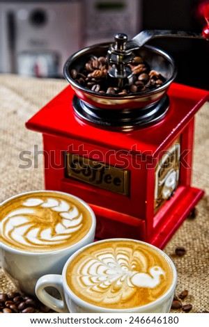 Picture of coffee cups in front of manual coffee grinder - stock photo