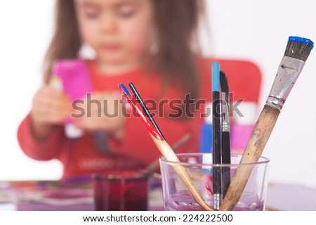 Picture of colorful painting utensils .The Girl in the background is unsharp. Short focus picture. Bokeh.