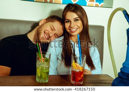picture of couple relaxing at the hookah bar with cocktails and man put his head on the shoulder of his girlfriend - stock photo