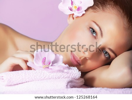 Picture of cute female with pink orchid flower in head lying down on massage table, healthy lifestyle, luxury spa resort, enjoying dayspa, aroma therapy, pampering and skin care concept - stock photo