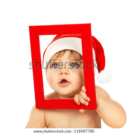 Picture of cute infant looking through red Christmas frame isolated on white background, little boy dressed in pretty Santa Claus hat, winter holidays, xmas celebration, New Year eve, happy childhood - stock photo