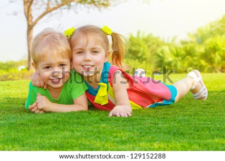 Picture of cute little girl with pretty boy lying down on green grass in park, cheerful children resting on the field on backyard, brother and sister having fun outdoors in springtime, happy childhood - stock photo