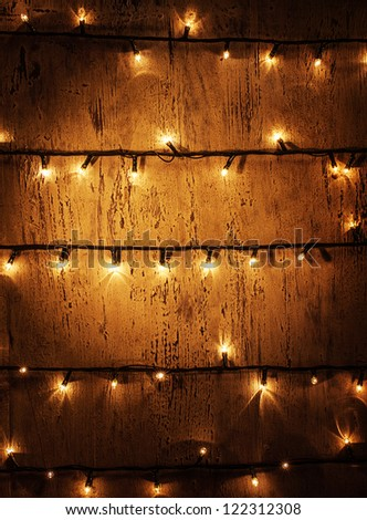 Picture of decorated door, abstract background, vintage wooded wall with glowing shining Christmas lights, decorative garland, festive electric festoon, New Year illuminated home ornament - stock photo