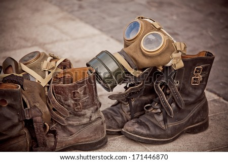 Picture of dirty old used boots and a gasmask