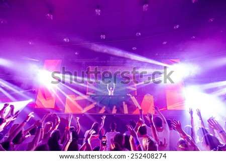 Picture of dj concert, music festival, party in nightclub, dance floor, disco club, many people standing with raised hands up and clapping, happiness and night life concept.
