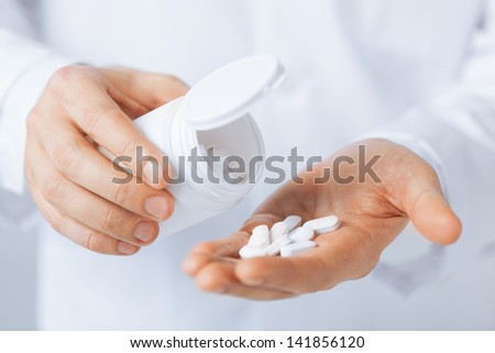 picture of doctor hands holding white pack and pills - stock photo