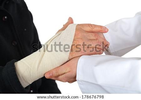 Picture of doctor's hand making a bandage for an elderly hand - stock photo