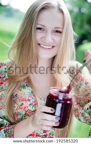 picture of eating strawberry jam from glass jar beautiful blond young woman having fun happy smiling & looking at camera teenage girl on summer day outdoors background - stock photo