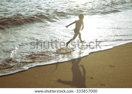 Picture of exciting little boy running on beach beside waves. Vintage image of kid in evening sunlights on seaside background. - stock photo